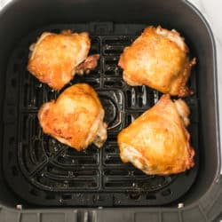 four cooked chicken thighs in the basket of an air fryer