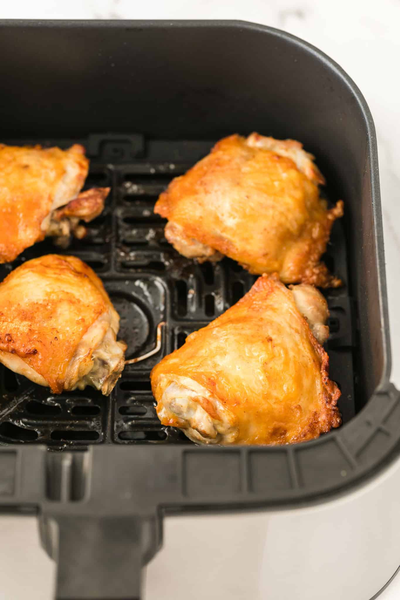 cooked chicken thighs in an air fryer ready to be served