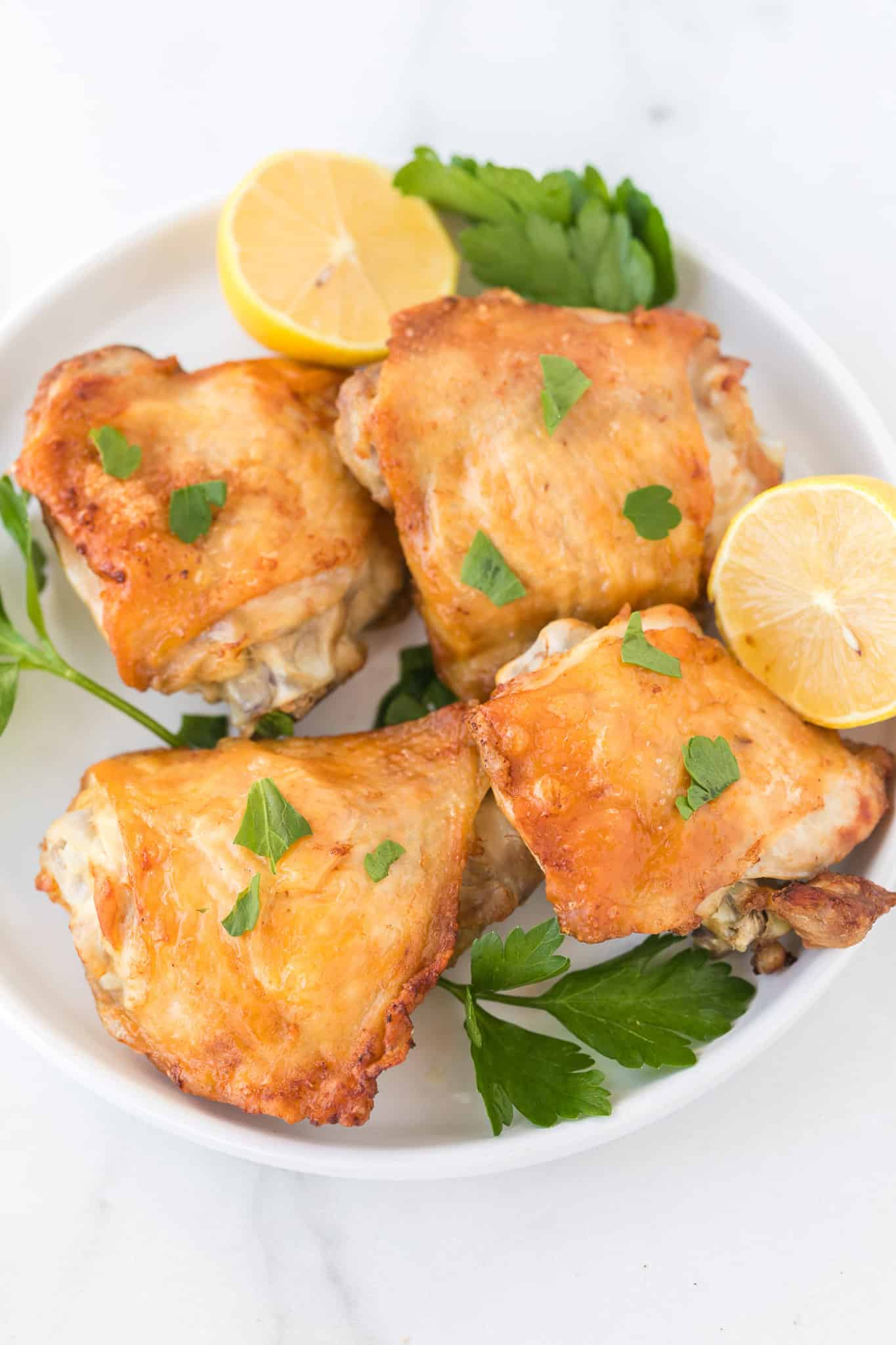 air fryer chicken thighs served on a plate with fresh lemon and parsley