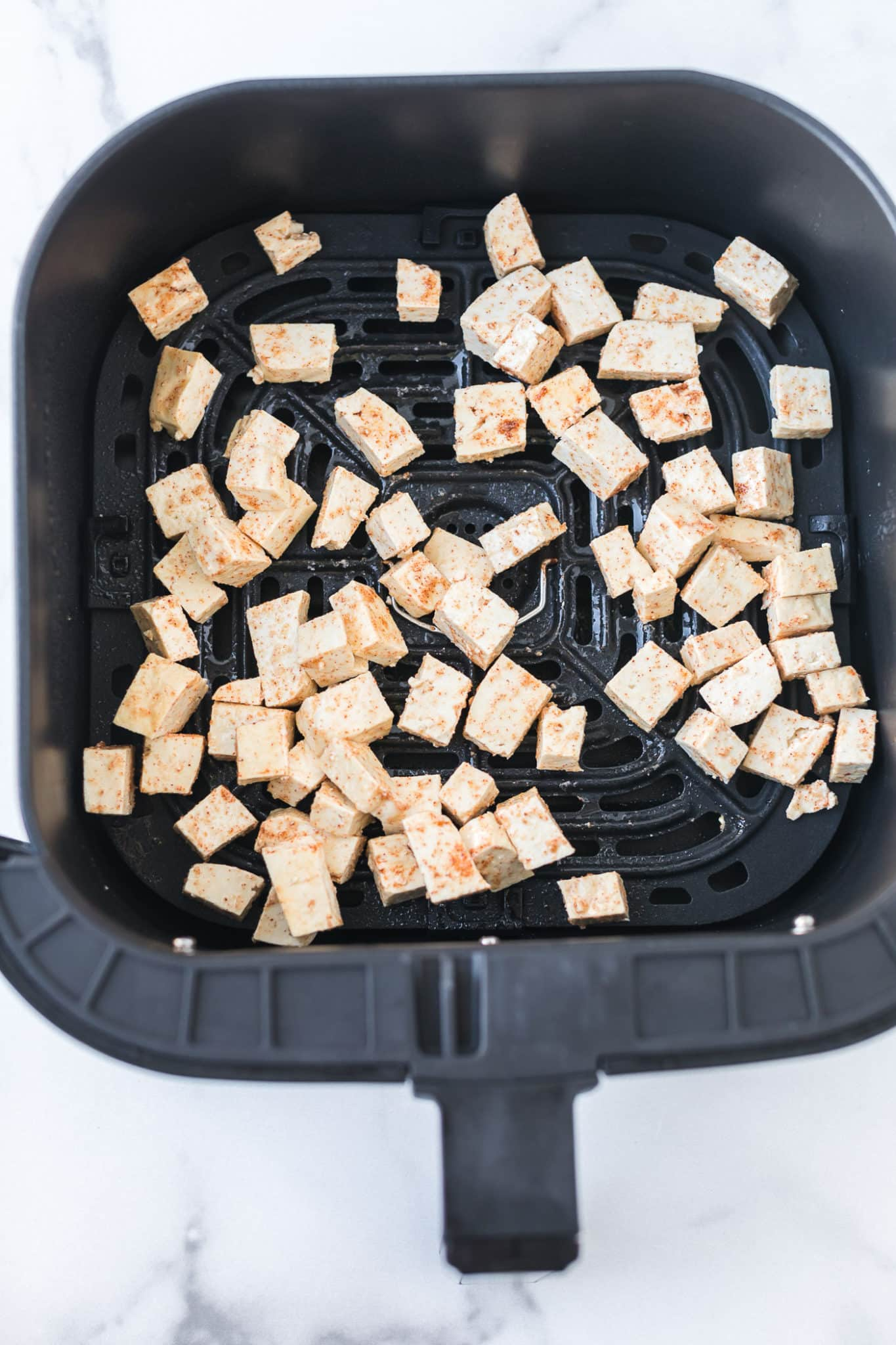 seasoned tofu in the basket of an air fryer ready to be baked
