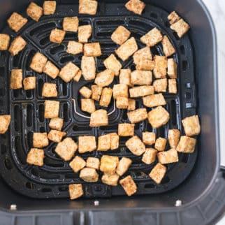 air fryer basket filled with crispy tofu