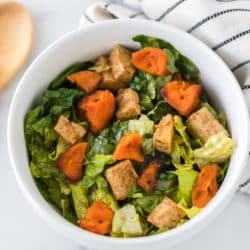 salad served in a white bowl with tofu and roasted sweet potatoes