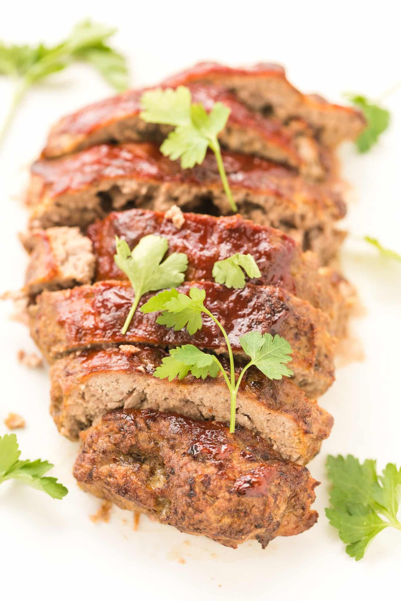 sliced air fryer meatloaf with a sprinkle of parsley on top