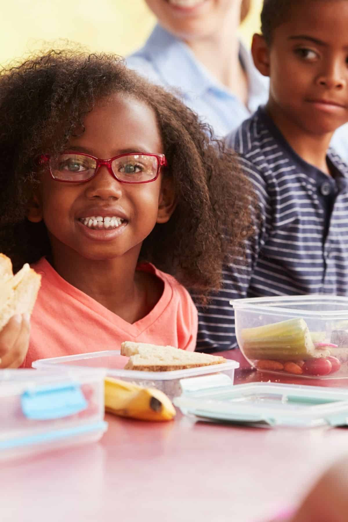young child in glasses eating lunch