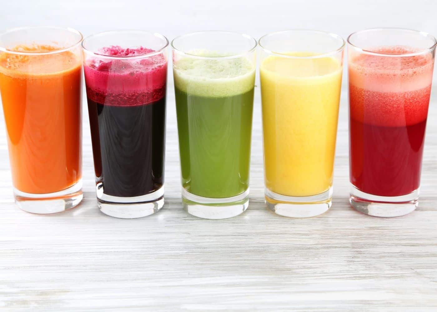 five colorful juices lined up on a table