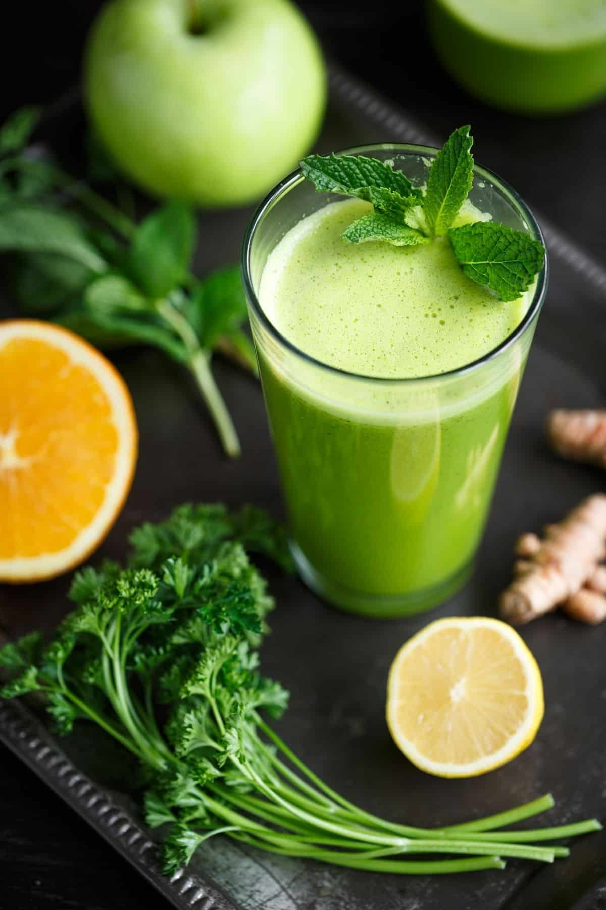 green juice served with mint, parsley, lemon, and apple