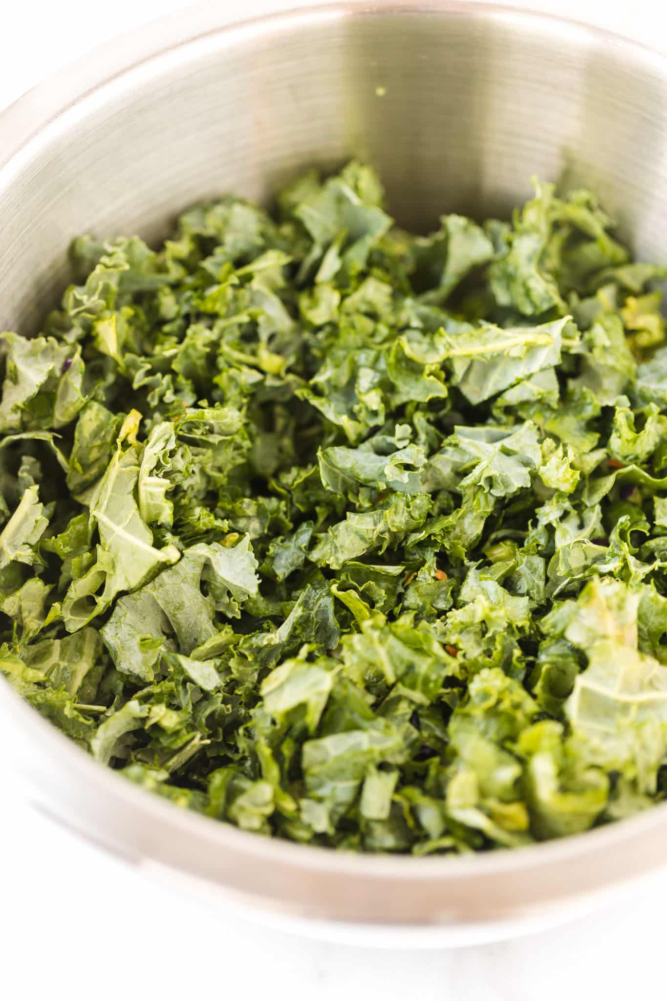 shredded green kale in a mixing bowl