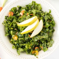 kale salad served in a white bowl topped with sliced pear