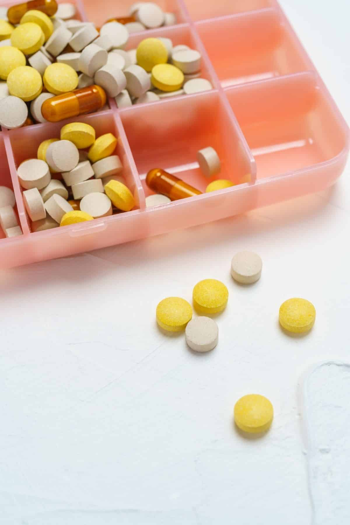 pink pill holder with tablets and capsules