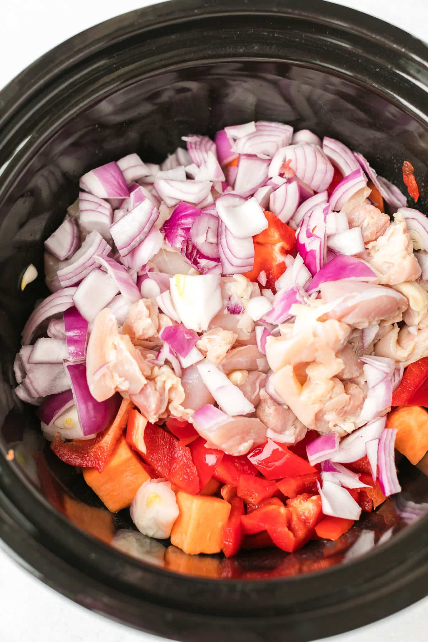 ingredients for chicken curry combined in a black slow cooker