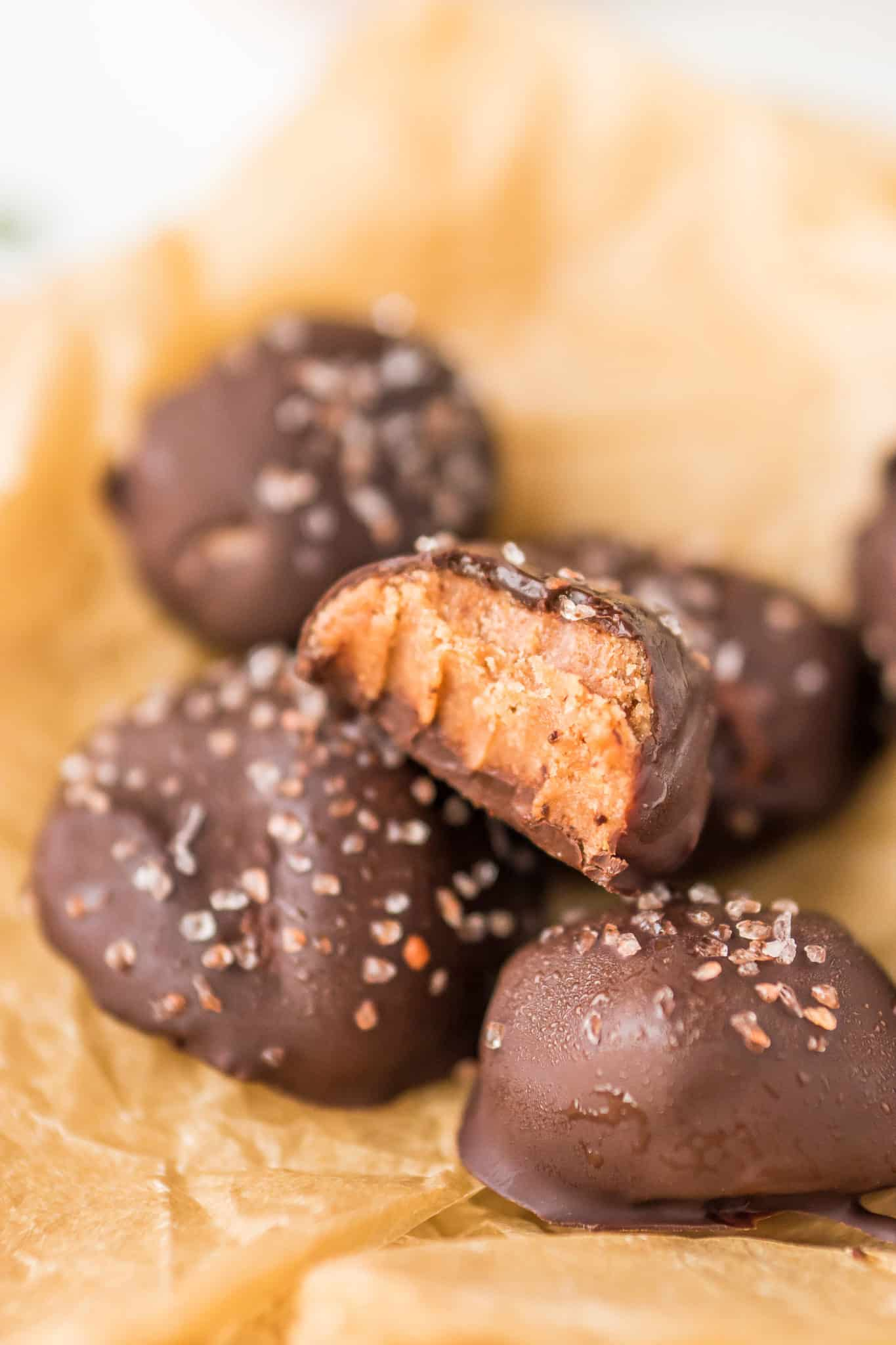 stack of chocolate tahini truffles with a bite taken out of one