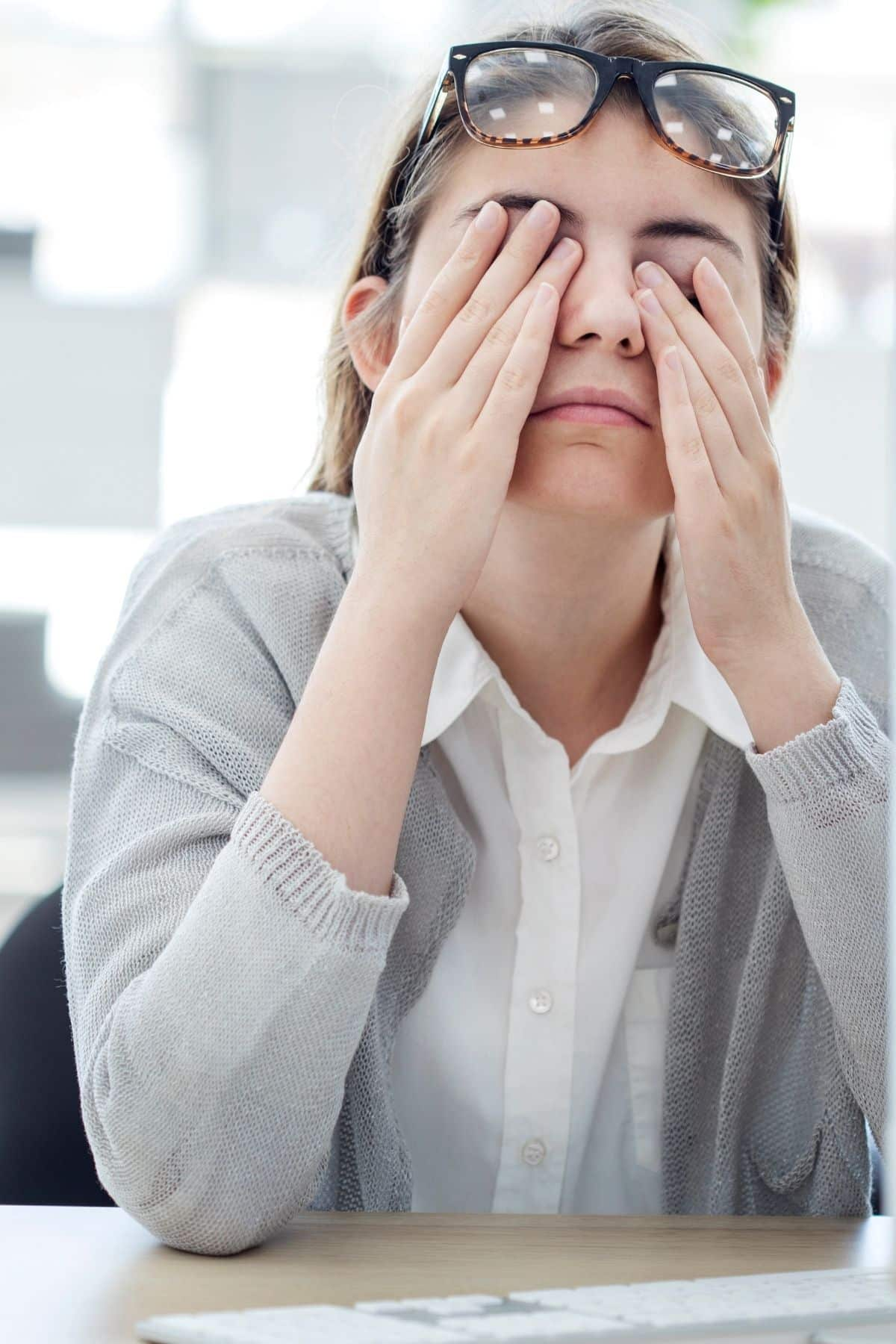 tired woman holding her hands over her eyes