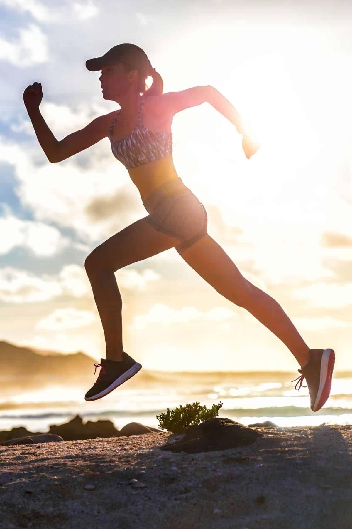 female athlete sprinting on a beach