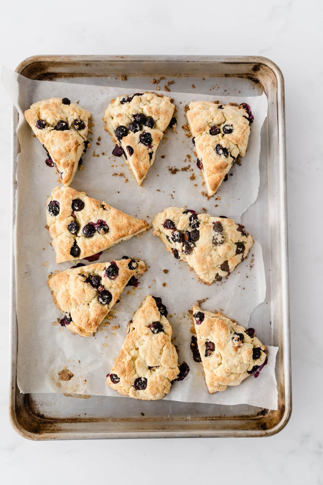 baked blueberry scones on a baking sheet