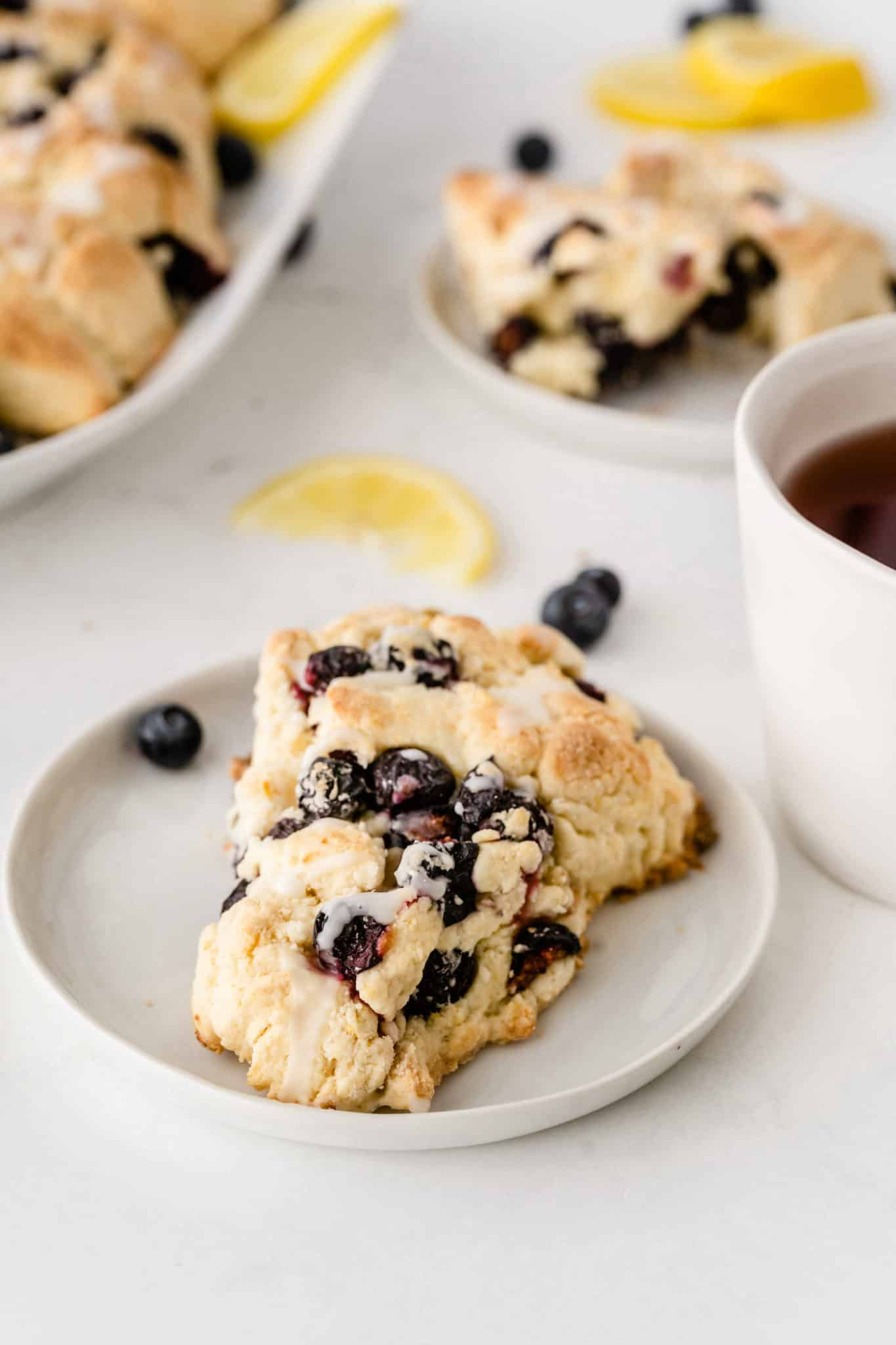 blueberry scone served on a plate with fresh blueberries and a cup of tea