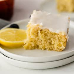slice of lemon cake on a plate with fresh lemon