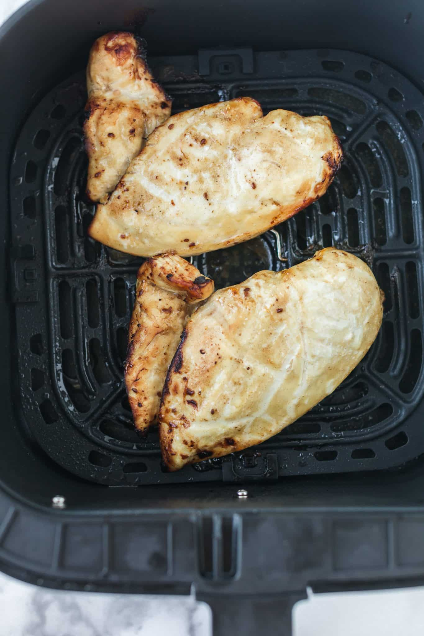 two chicken cutlets cooked in an air fryer basket