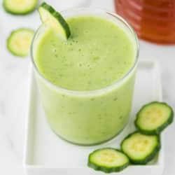 light green smoothie served in a glass garnished with cucumber slices