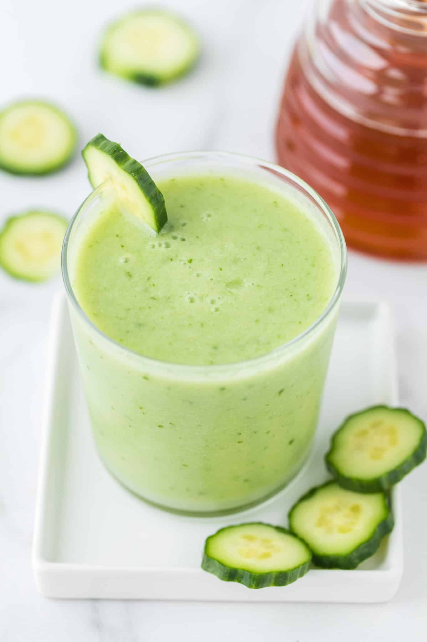 cucumber smoothie served in a glass with slices of fresh cucumber