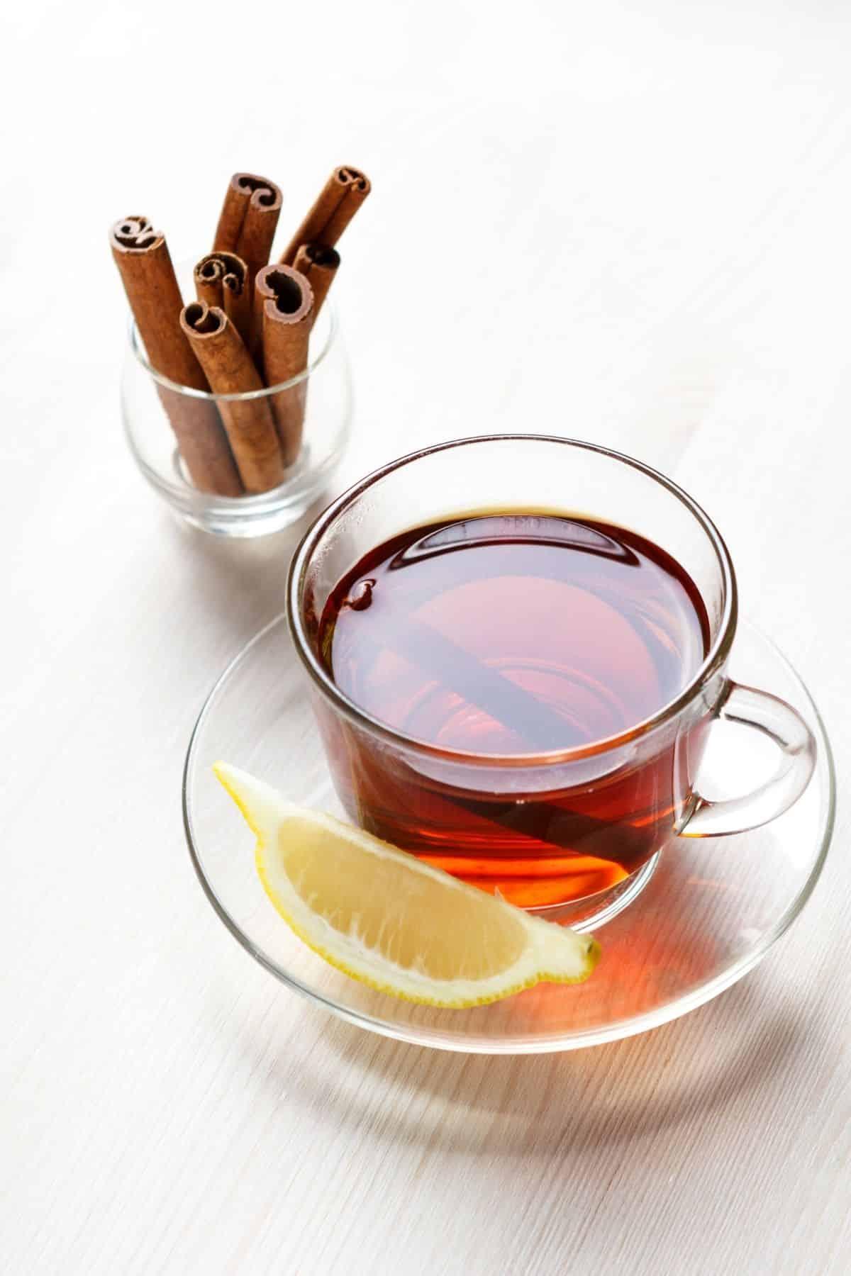 cinnamon tea served in a glass mug with a slice of fresh lemon