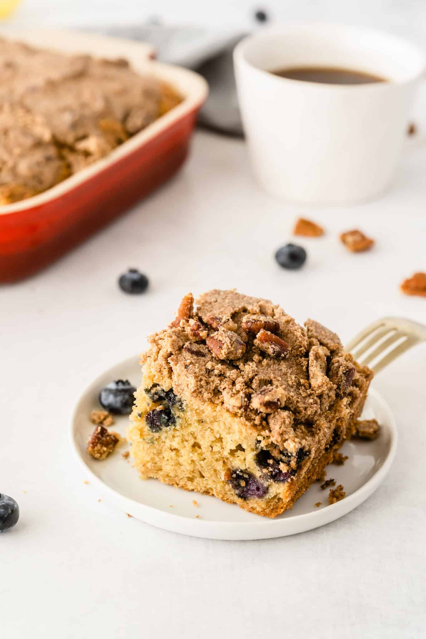 slice of blueberry coffee cake served with with a cup of coffee