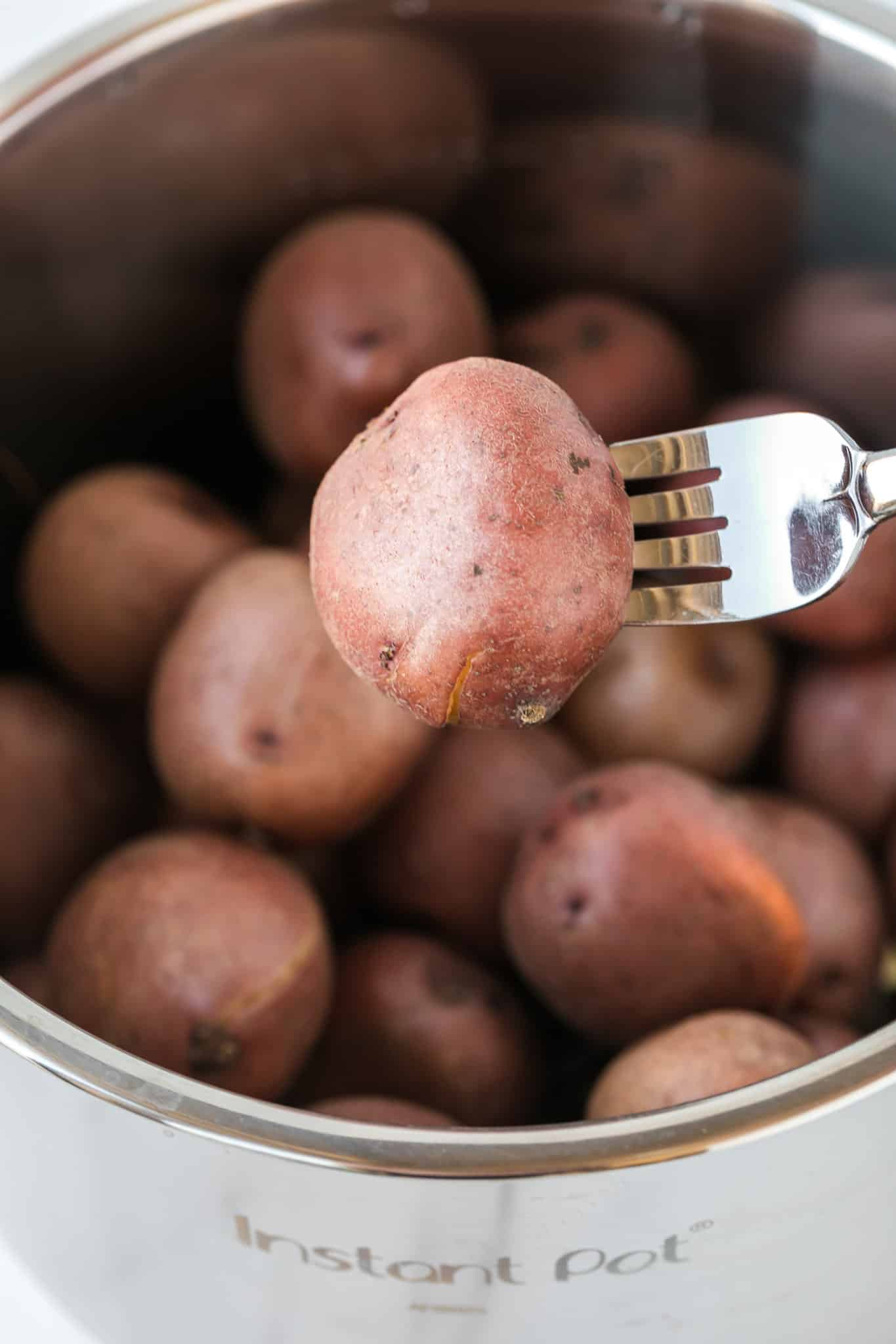 fork pricking a boiled potato in an instant pot pressure cooker