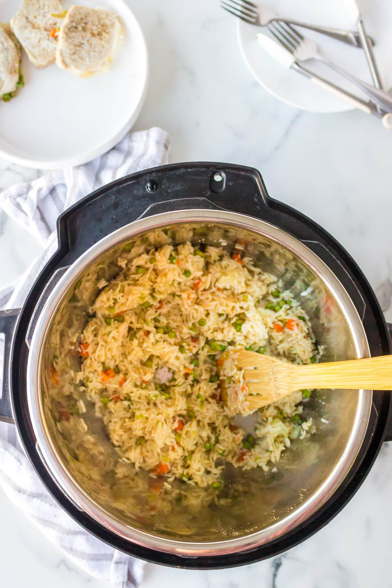 cooked rice and veggies in an instant pot pressure cooker, with the cooked pork on the side
