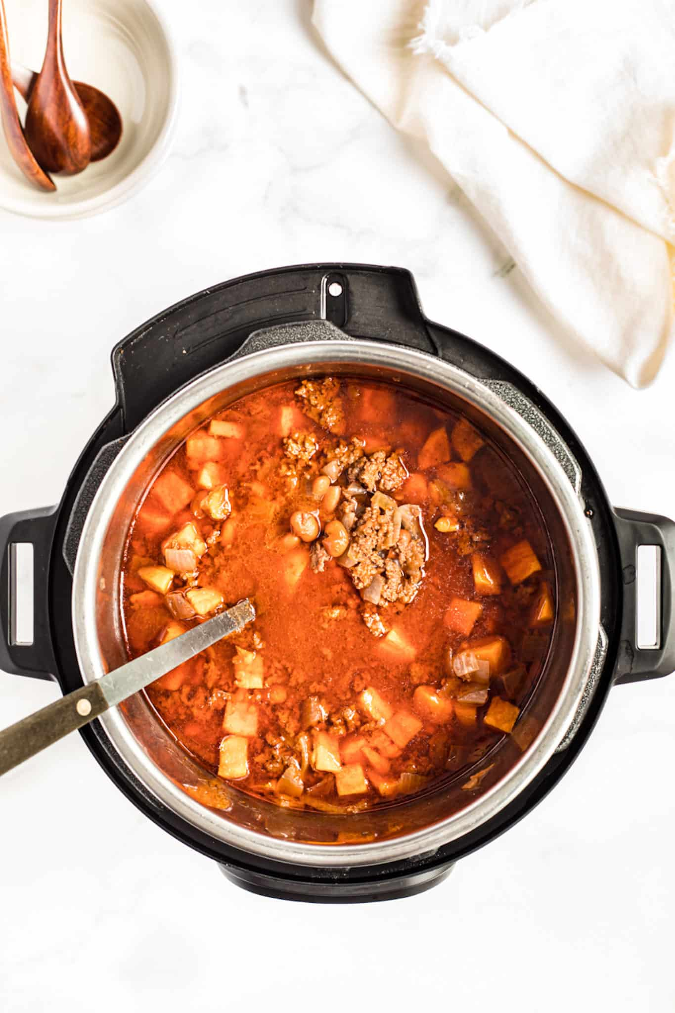 cooked sweet potato chili in an instant pot pressure cooker with a serving spoon