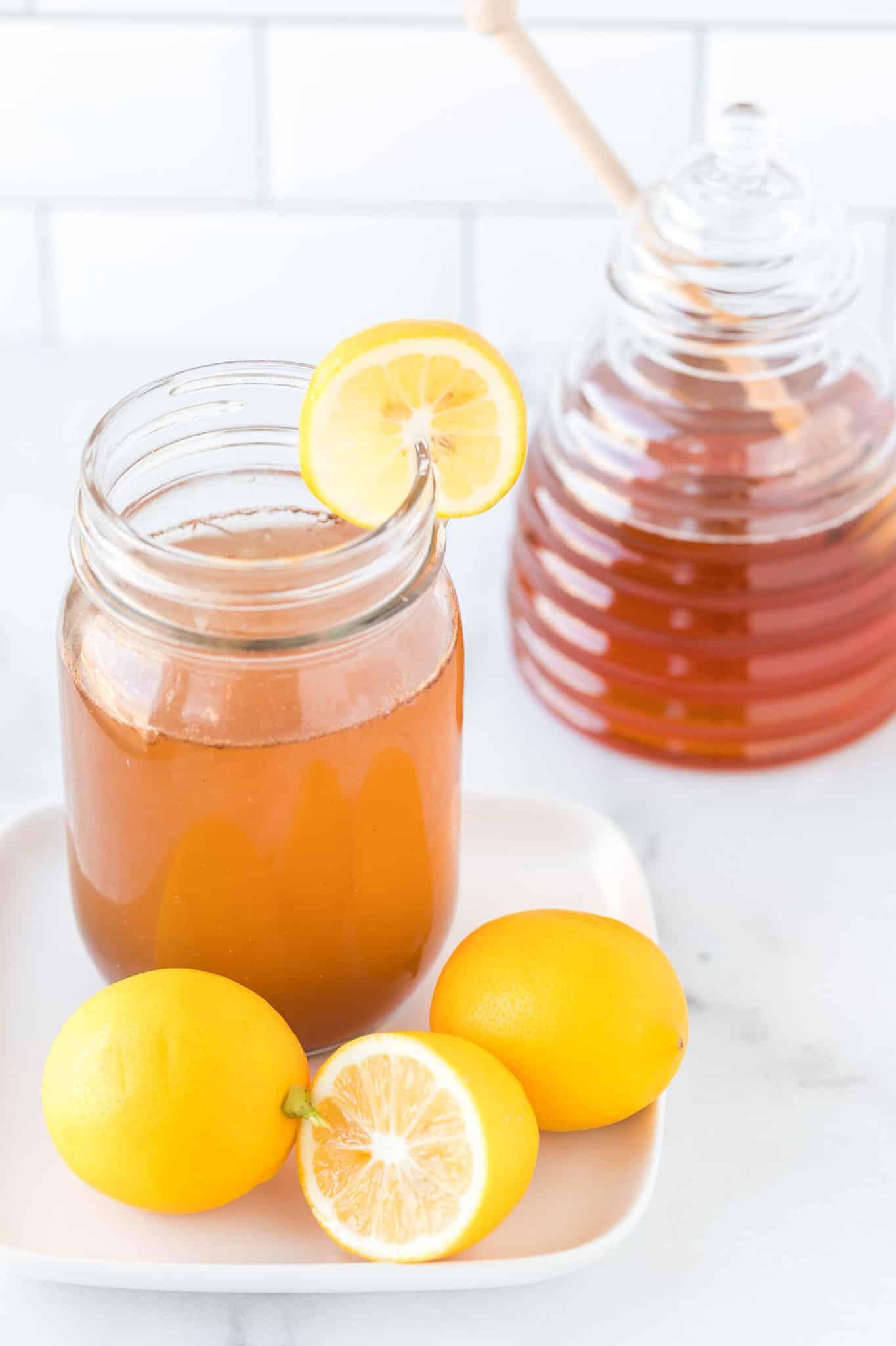mug filed with lemon cinnamon water on a plate with fresh lemon slices