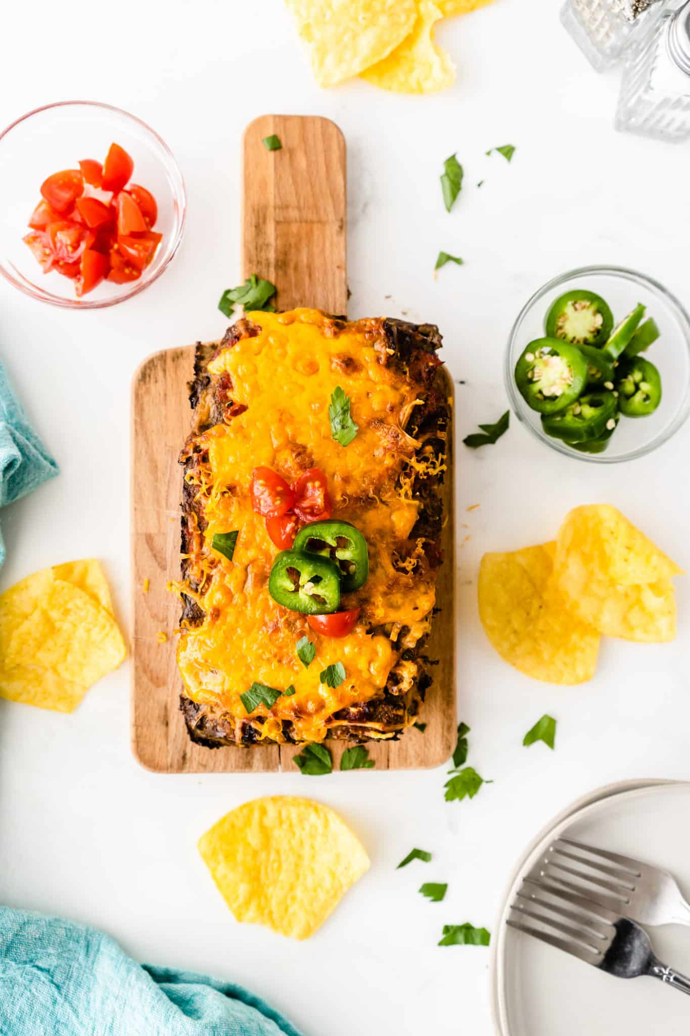 cooked taco meatloaf served on a wooden cutting board with extra toppings