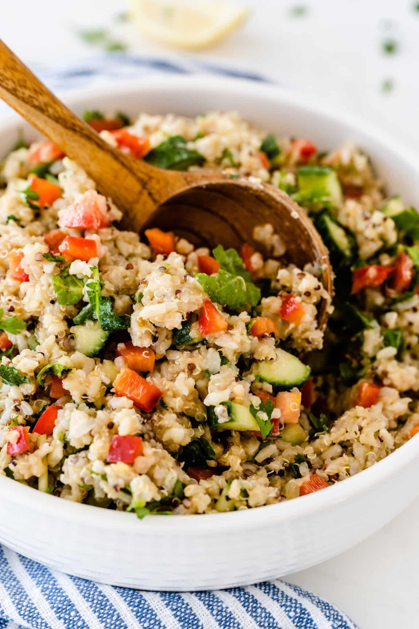 wooden spoon stirring a bowl of copycat costco quinoa salad