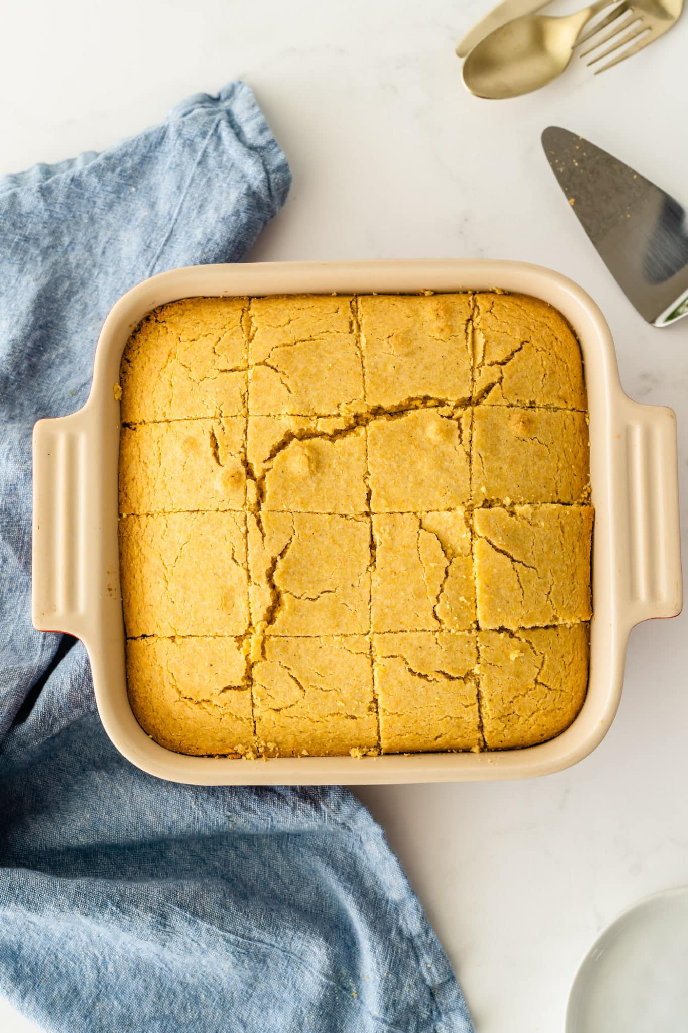 cornbread cooked in a square baking dish cooling on a countertop