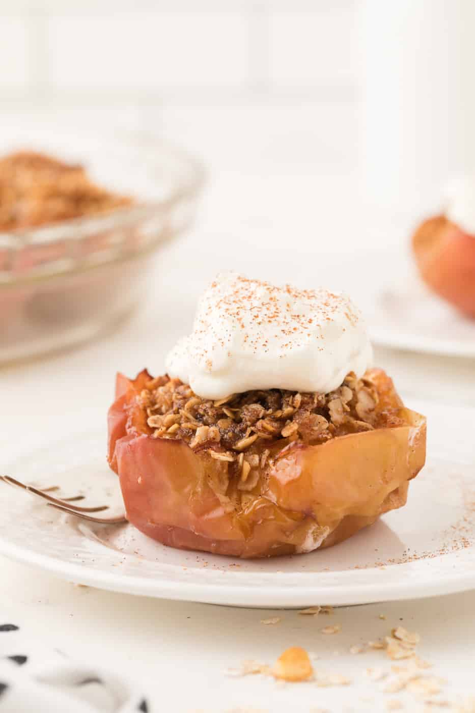 A baked apple with oat topping and whipped cream