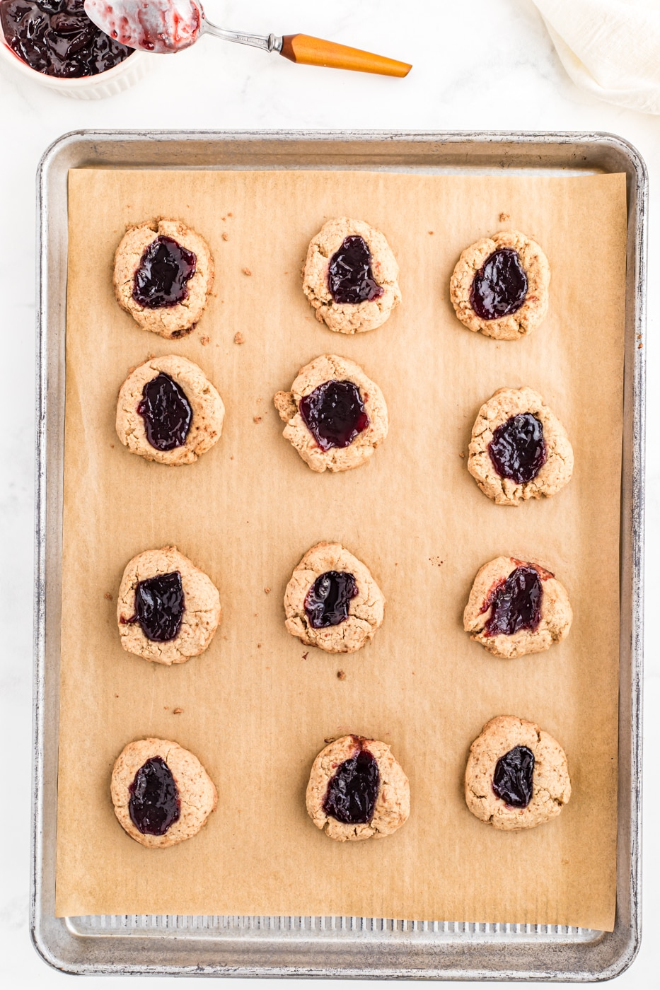 jam-filled thumbprint cookies on a baking sheet for oven