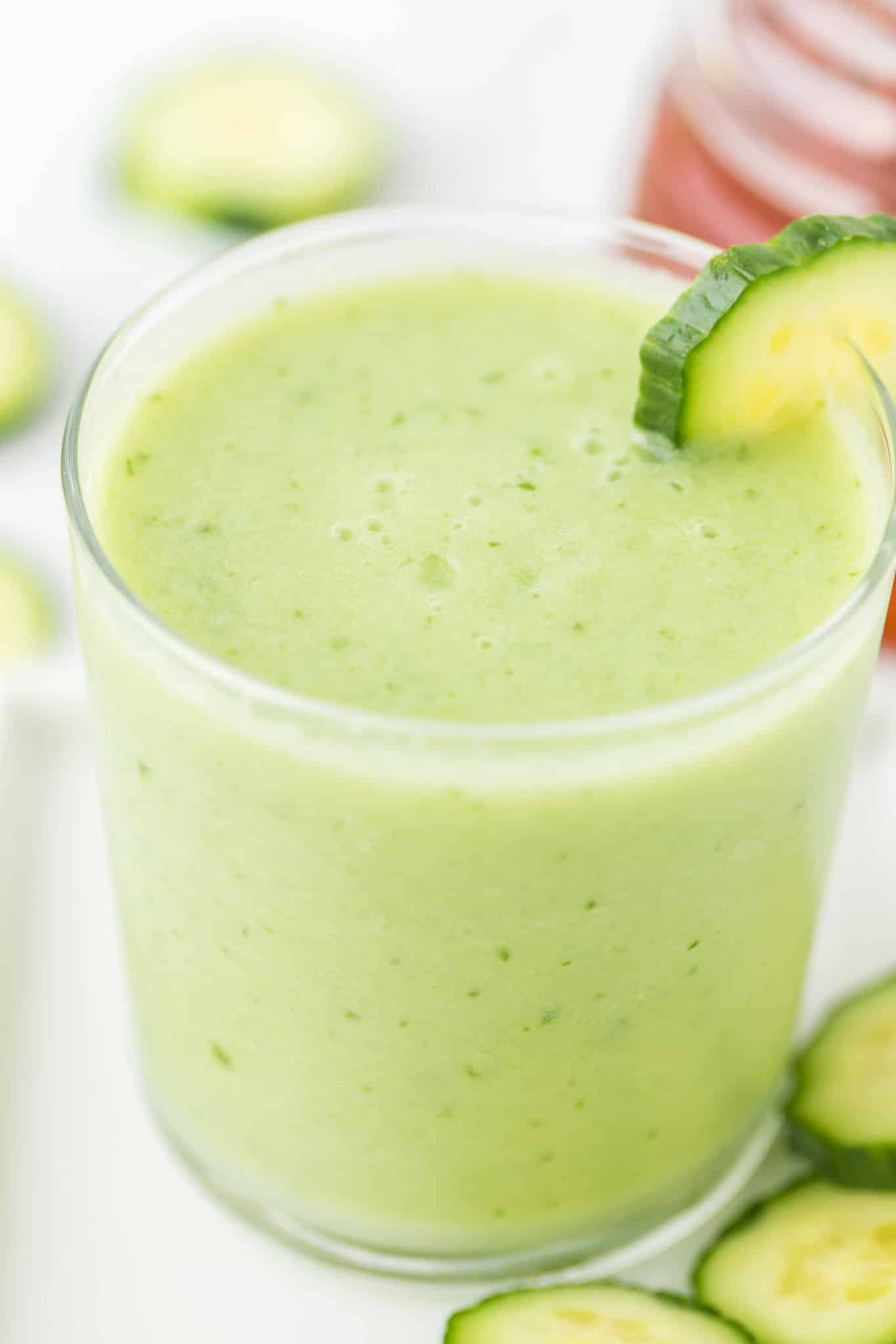 glass filled with light green cucumber smoothie with a slice of fresh cucumber on the edge