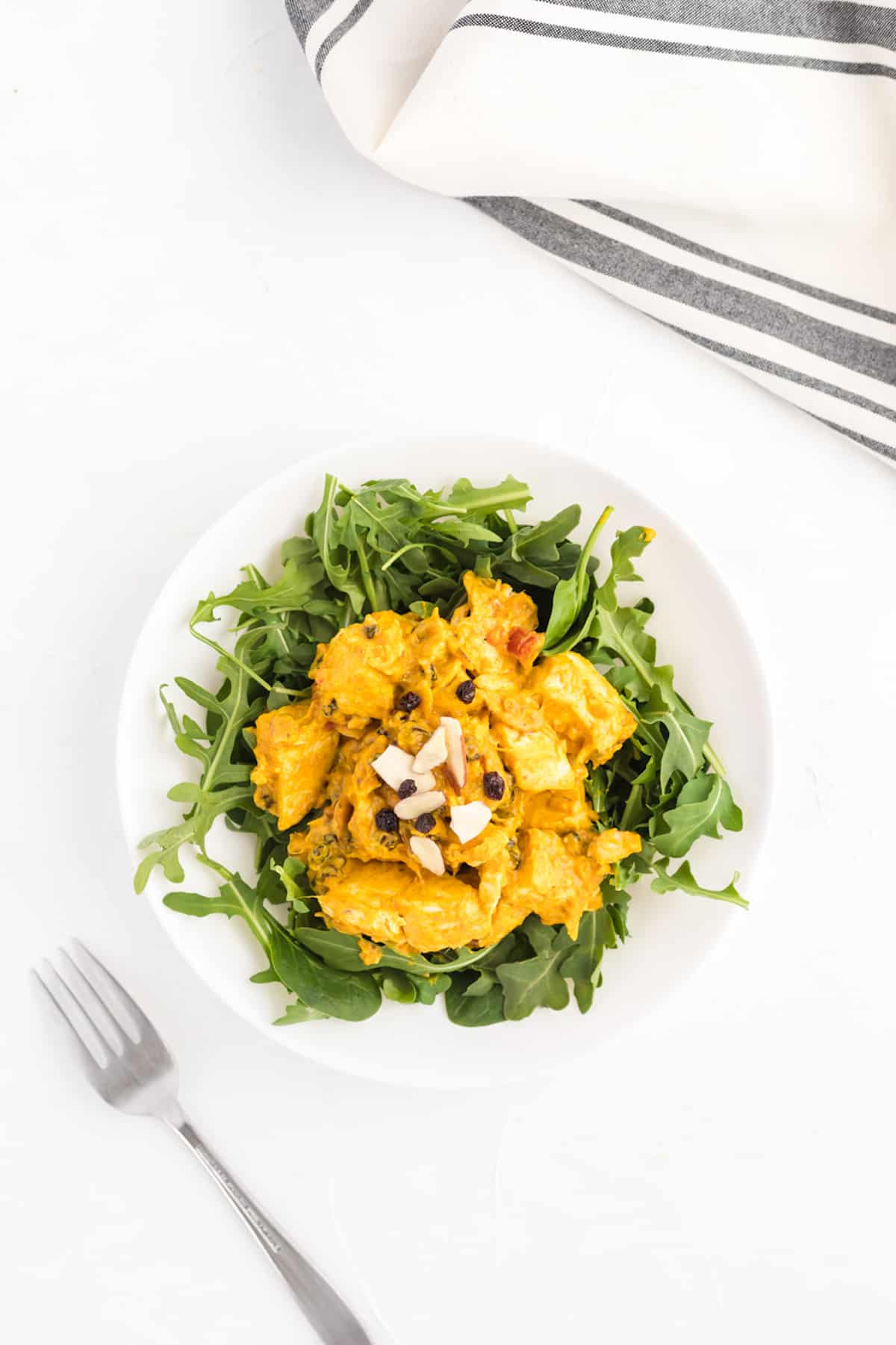 A plate of curry chicken salad on arugula