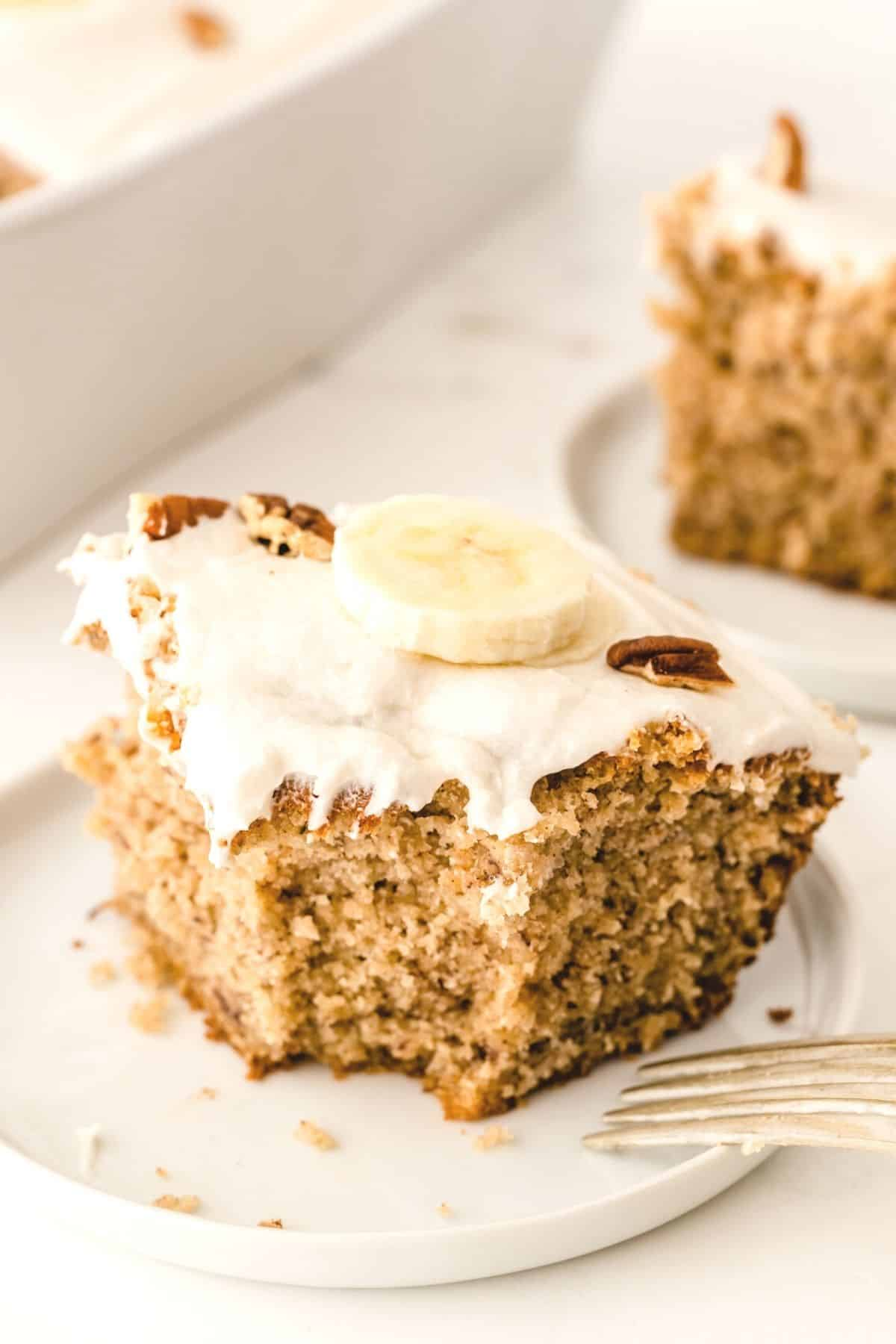 A slice of gluten-free banana cake on a white plate with fork
