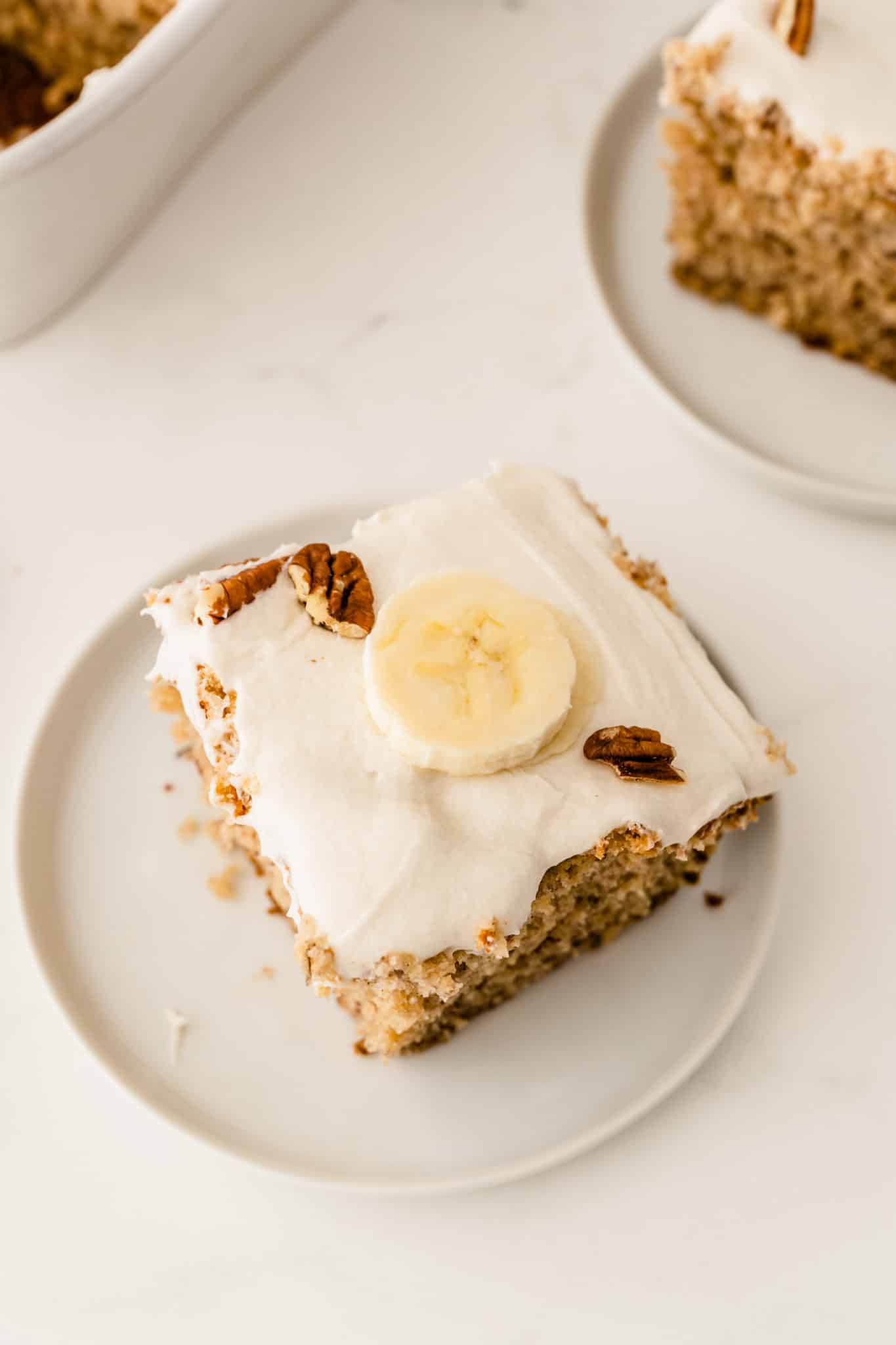 square slice of banana cake with a piece of banana on top