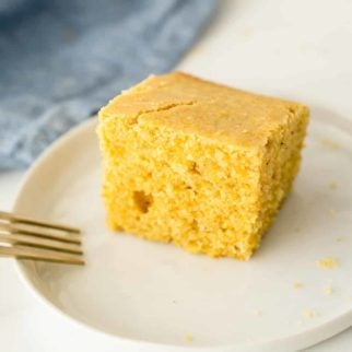 A piece of gluten free cornbread on a small plate