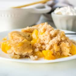 A plate of peach cobbler with a bowl of whipped cream behind it.