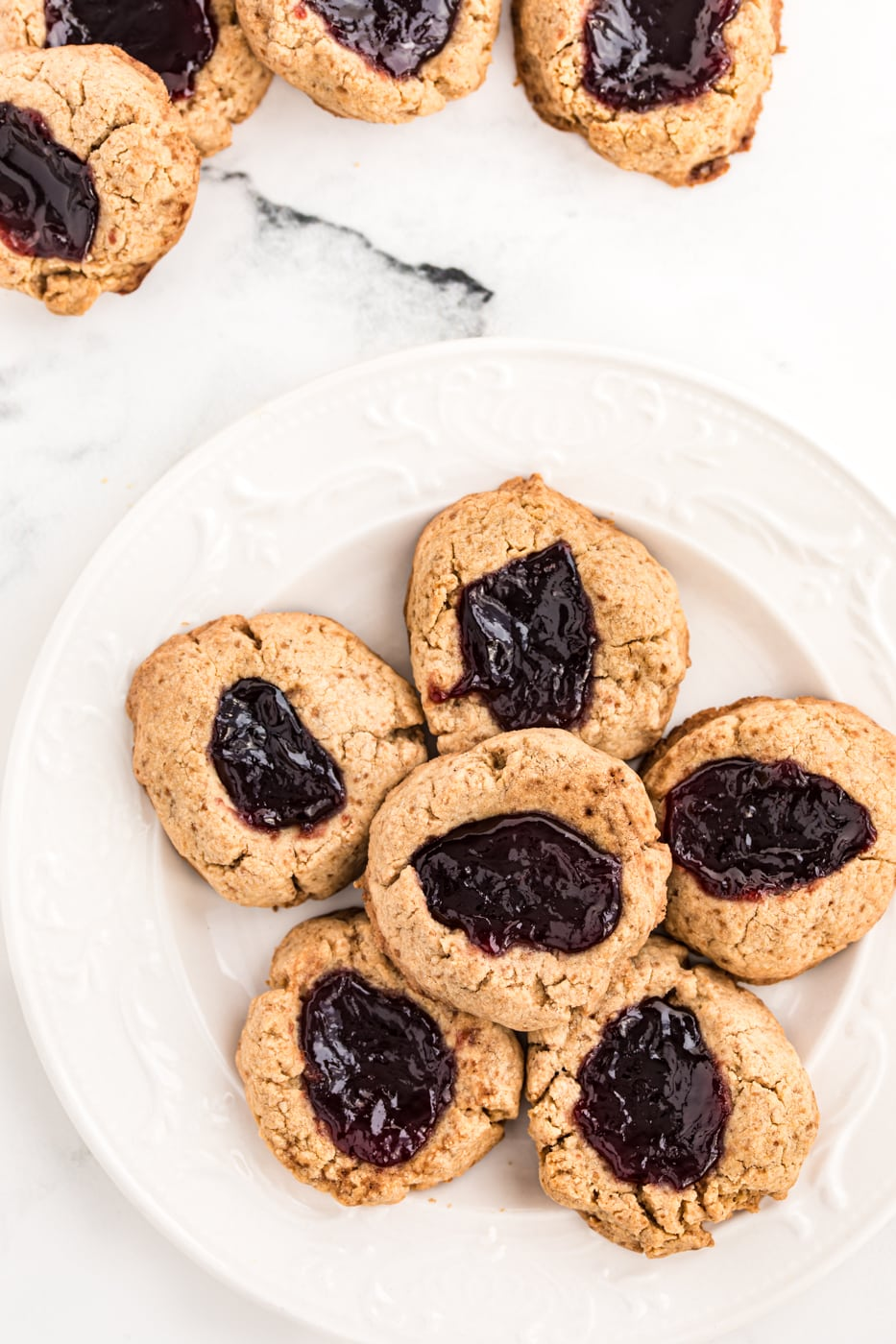 A plate of thumbprint cookies with jam