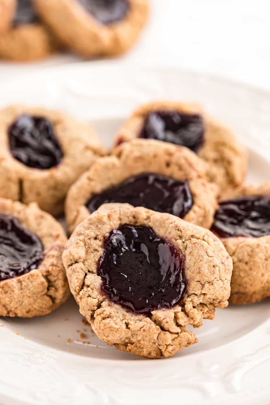 A close up photo of jam thumbprint cookies on a white plate