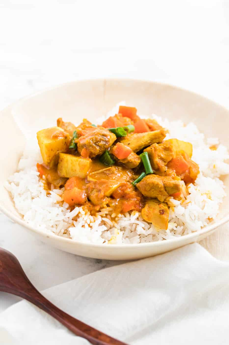 instant pot chicken curry with carrots and potatoes served in a bowl with steamed white rice