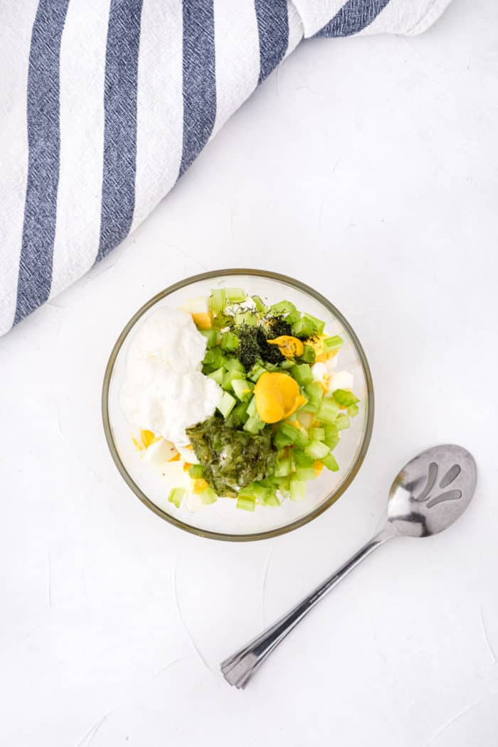 A bowl of ingredients for egg salad