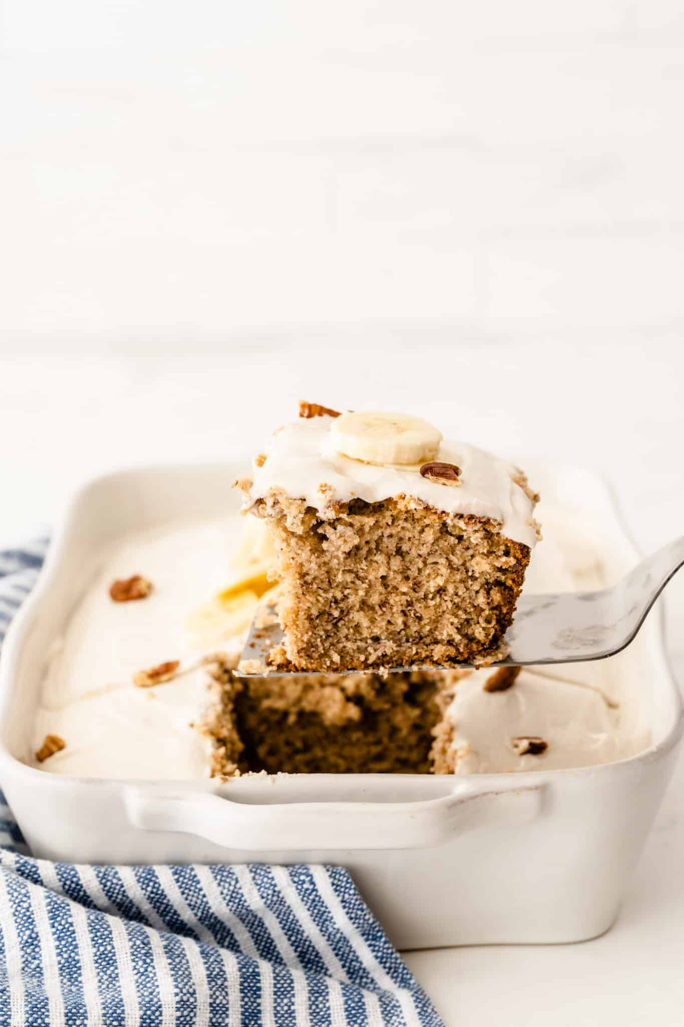 A slice of gluten-free banana cake with vanilla frosting