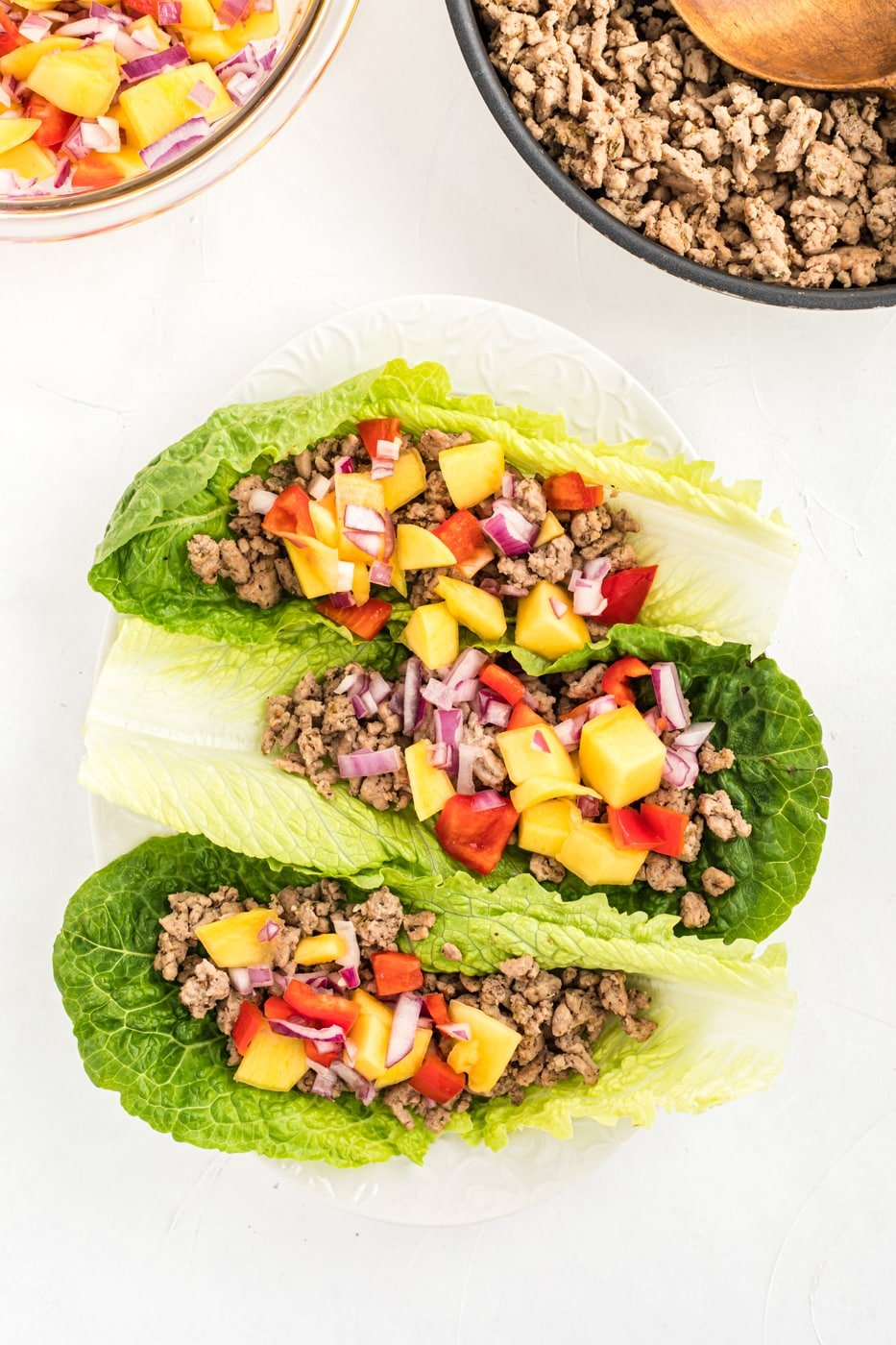 ground chicken lettuce tacos on a plate with mango salsa