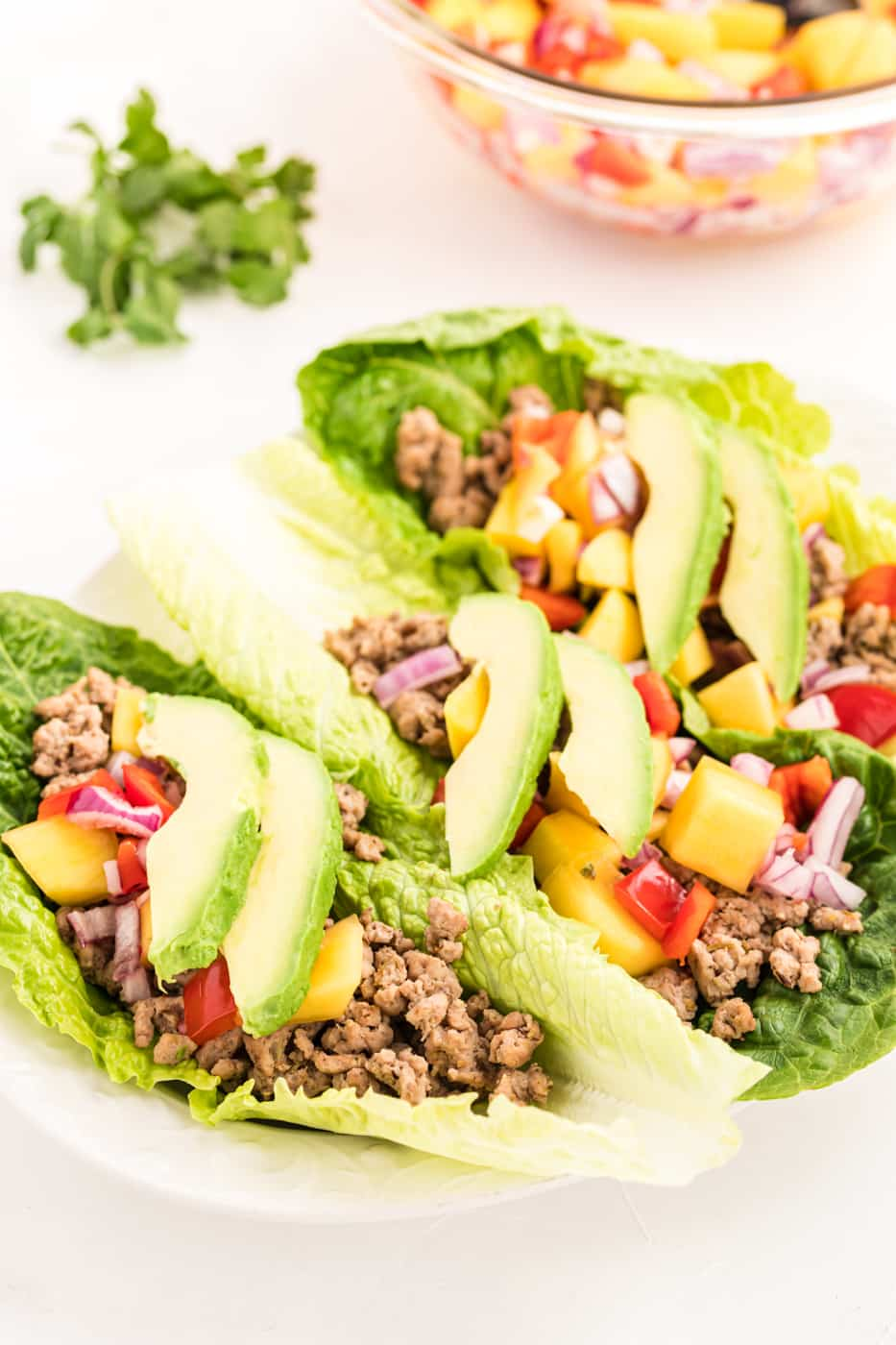 Ground chicken lettuce tacos with mango salsa and avocado