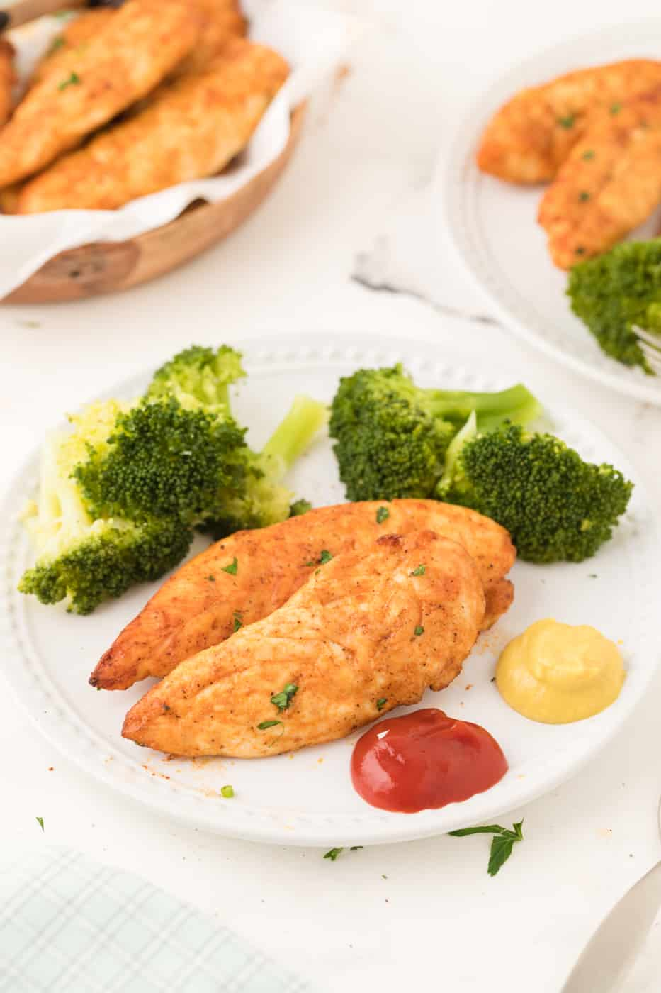 A plate of chicken tenders served with broccoli