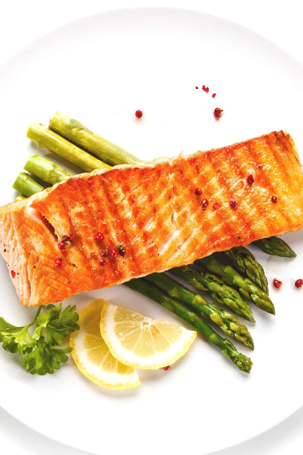 air fryer salmon served on a plate with asparagus and lemon