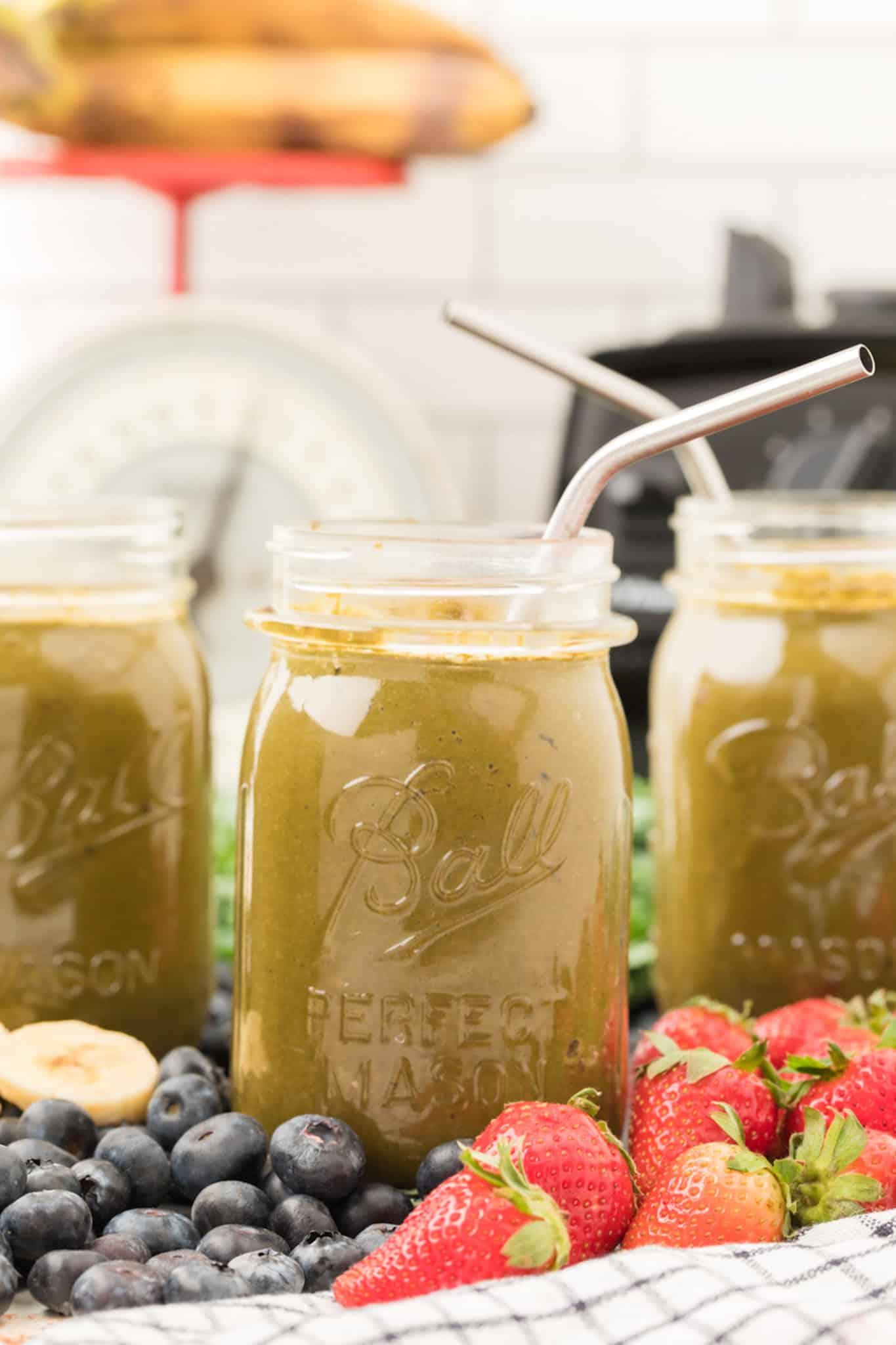 collard green smoothie served in jar with metal straws